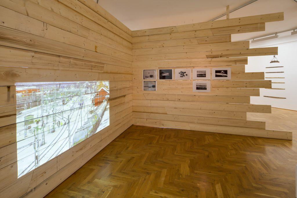 FLORIAN ZEYFANG: MEASURING POINT, (VERMESSUNGSPUNKT), 2012, Raumskulptur aus Fichtenholz, 7 Fotografien GHOSTTRAIN, (GEISTERZUG), 2012, HD Video, 20 min. Foto: David Brandt