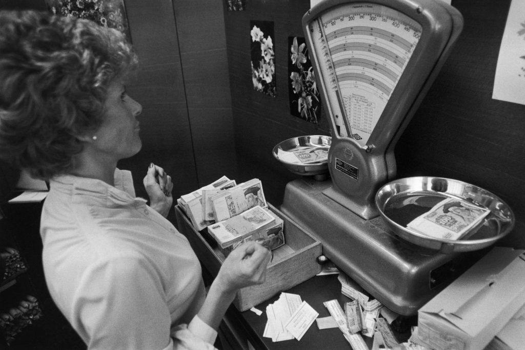 Deutsche Bank Frankfurt, 1979 – eine Bankangestellte kontrolliert das Gewicht von Banknoten, um eventuell gefälschte Scheine zu entdecken